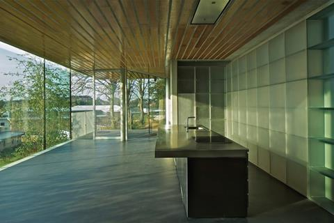 The south-facing kitchen is framed by a cast resin storage wall by Vincent de Rijk.